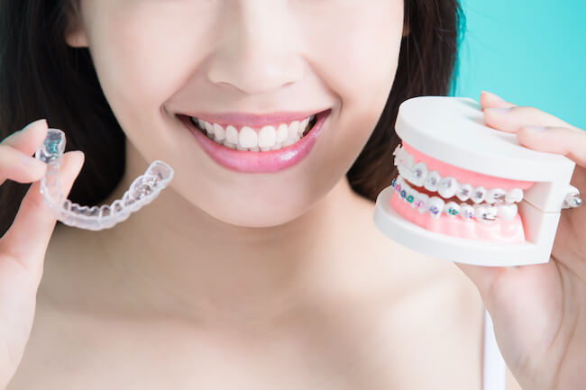 Girl holding braces in one hand and an Invisalign aligner in the other