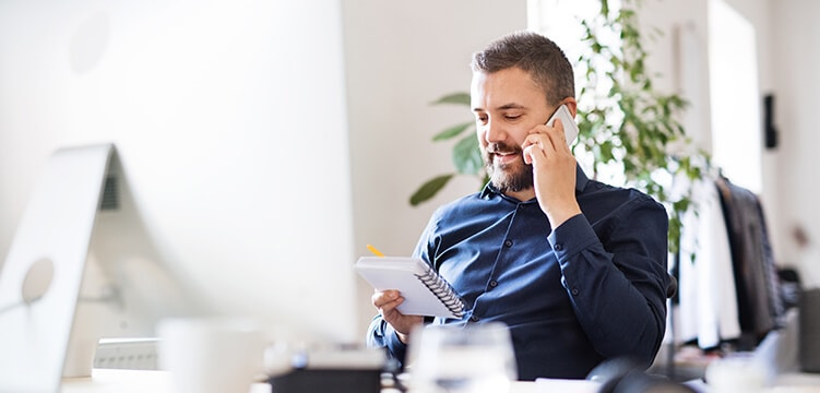 A bearded man sitting in the office while talking on the phone and holding a notepad