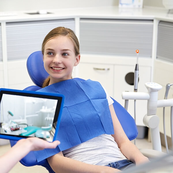 A blond girl in the dental office smiling while the doctor shows her tablet to the camera