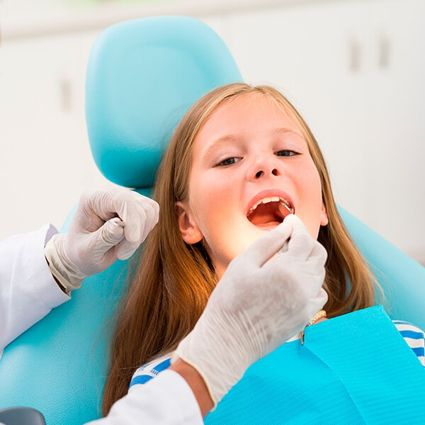 The dentist checking the mouth of a little girl who is sitting in the dentist's chair