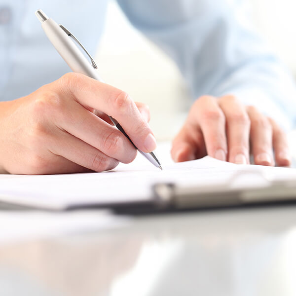 A close up shot of a person writing with a pen a paper